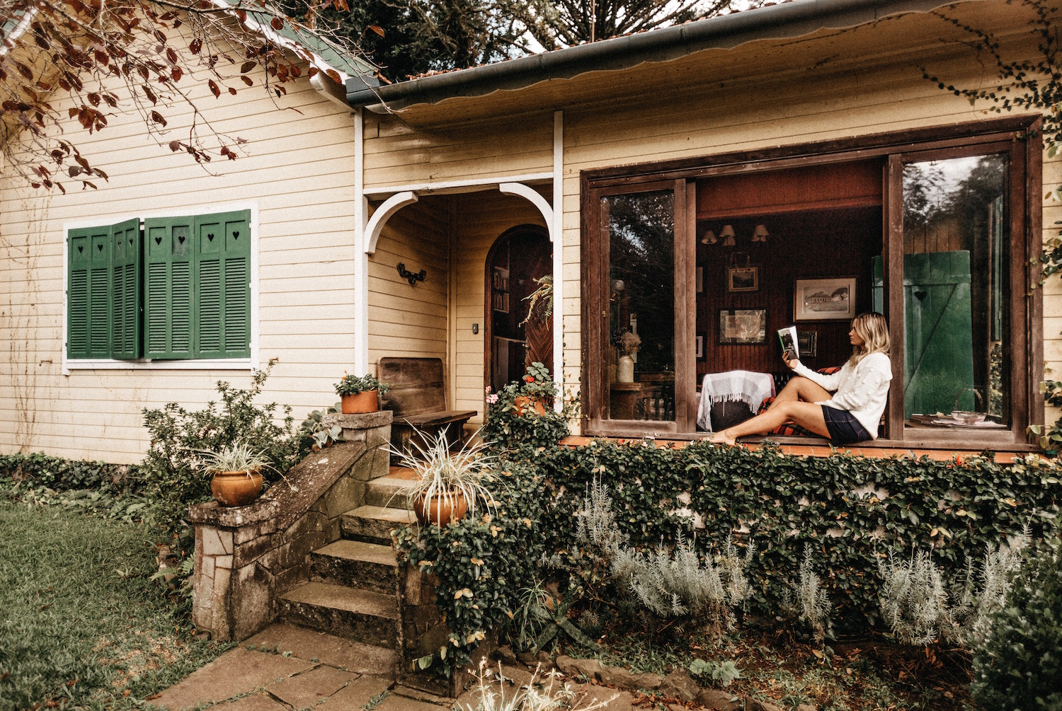 Woman sitting on a house porch alone, reading a book