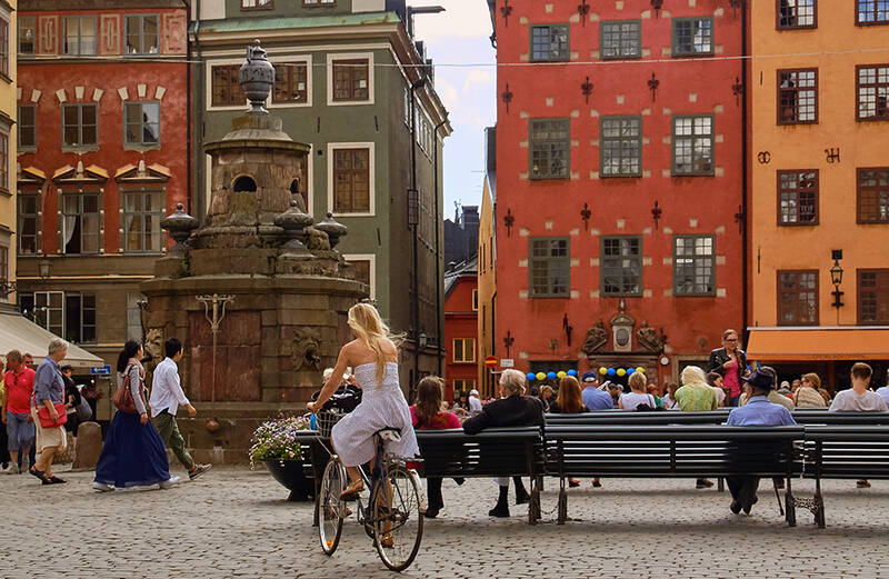 Stockholm streets with old buildings and woman on a bike